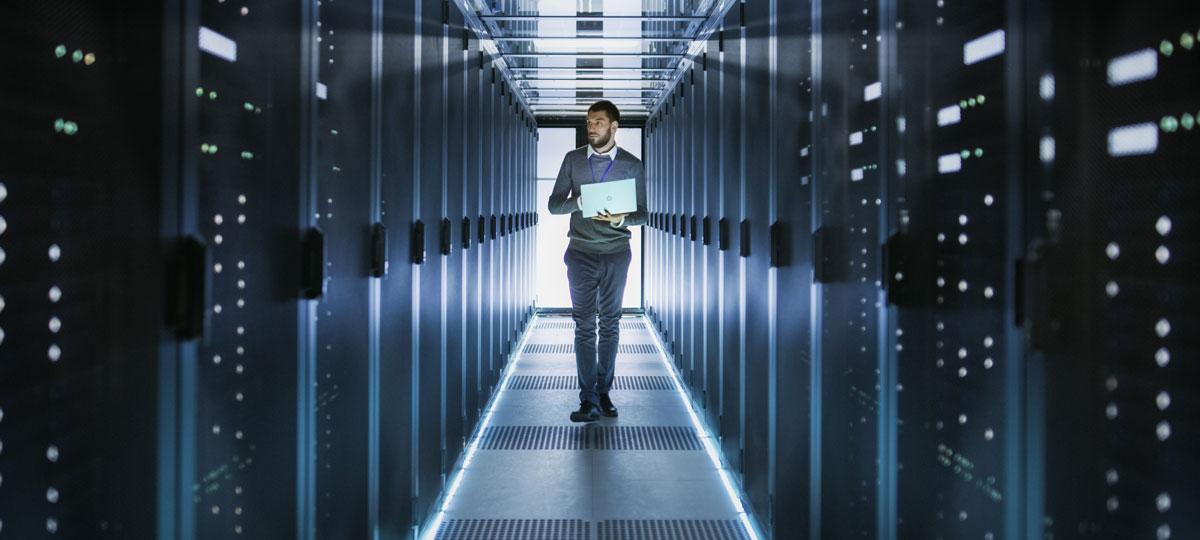 IT technician working on laptop in a data center full of rack servers